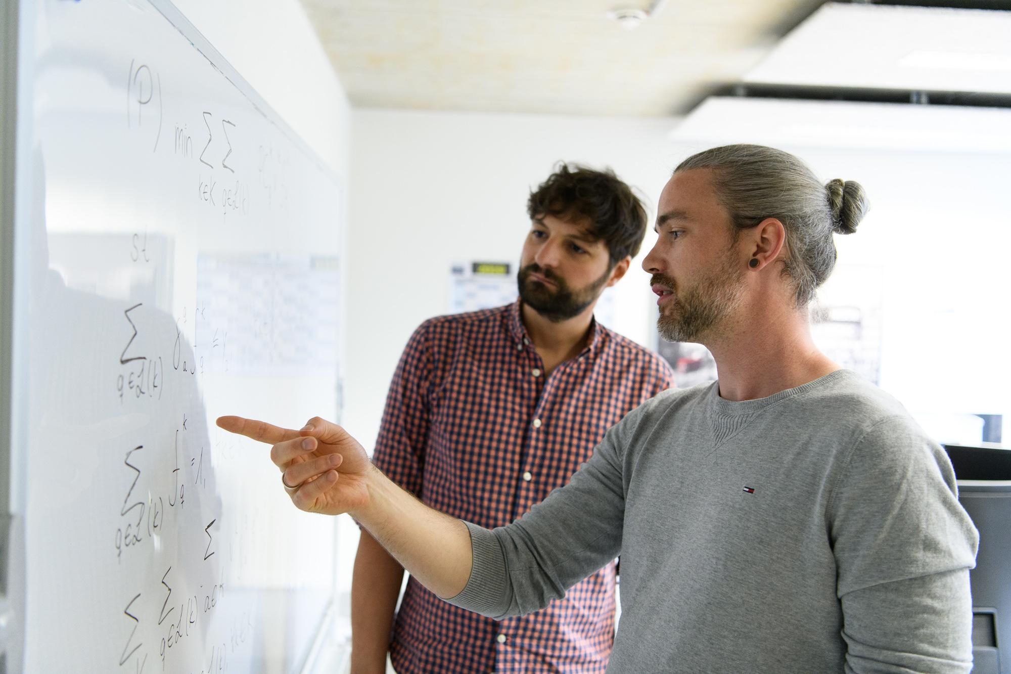 Mathemetische Optimierung - Zwei Data Scientists vor Whiteboard mit mathematischen Formeln