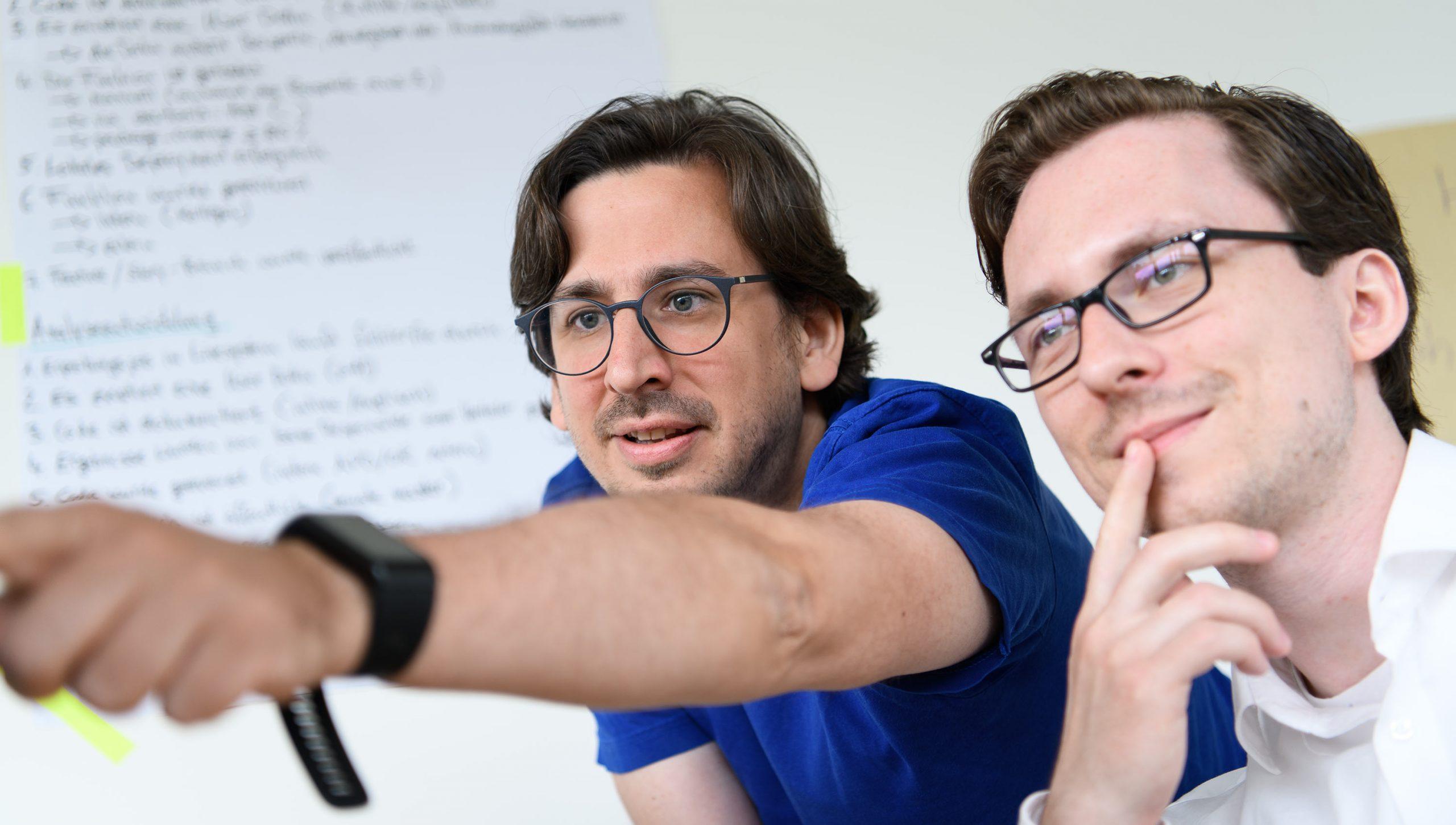 Kollegen zeigen etwas an einem Bildschirm
