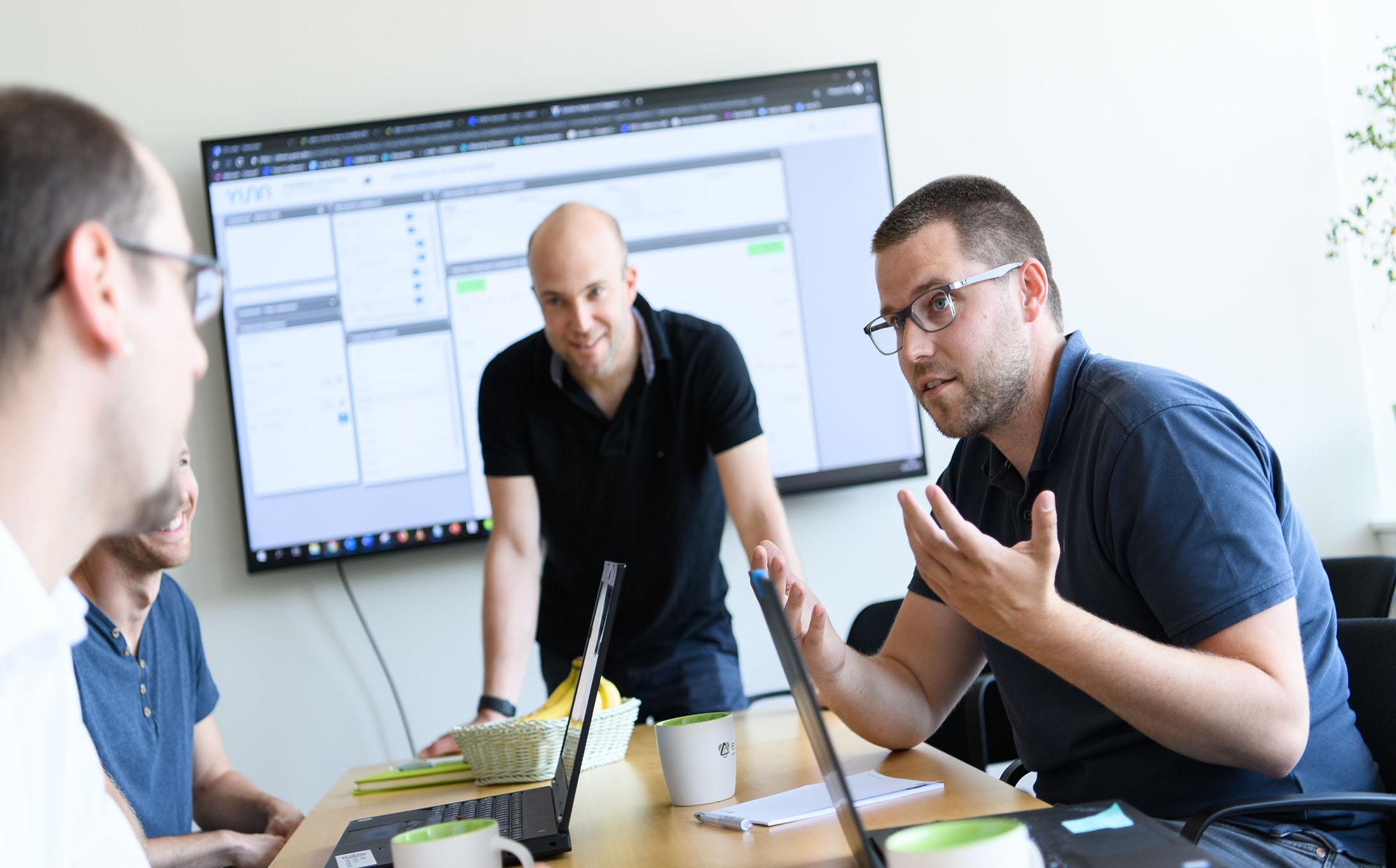 Personen besprechen sich bei der Softwareentwicklung